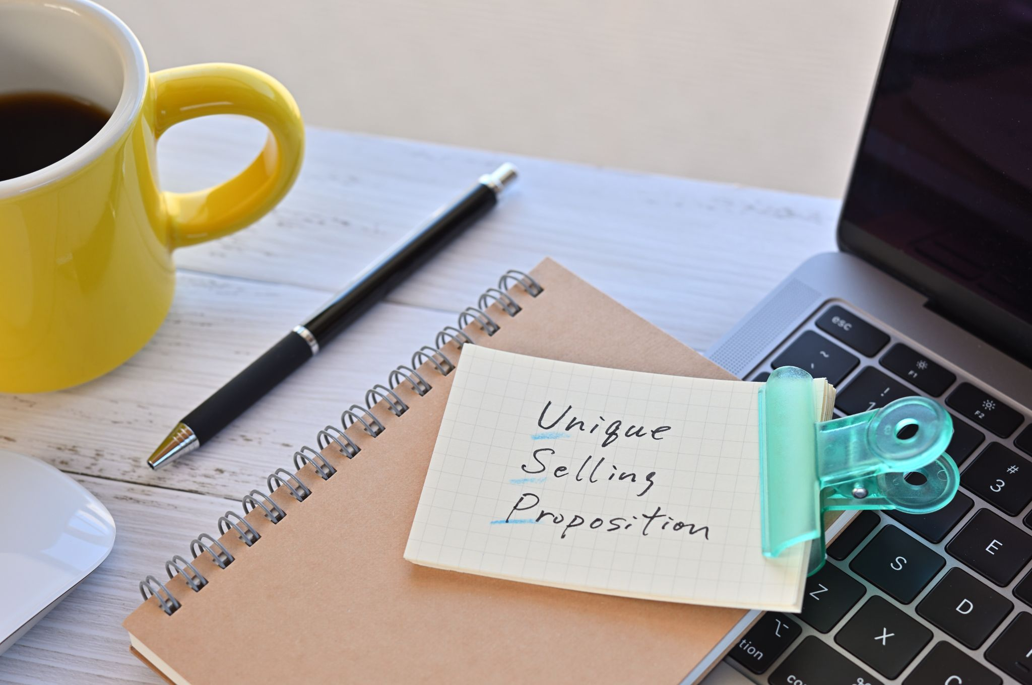Note with Unique Selling Proposition written on it sitting on top of brown notepad and laptop. Next to it there is a yellow cup of black coffee and black pen