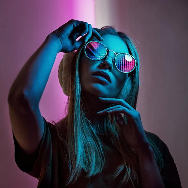 foto de uma mulher loira posando com a mão no rosto e de óculos escuro com luzes estilo neon