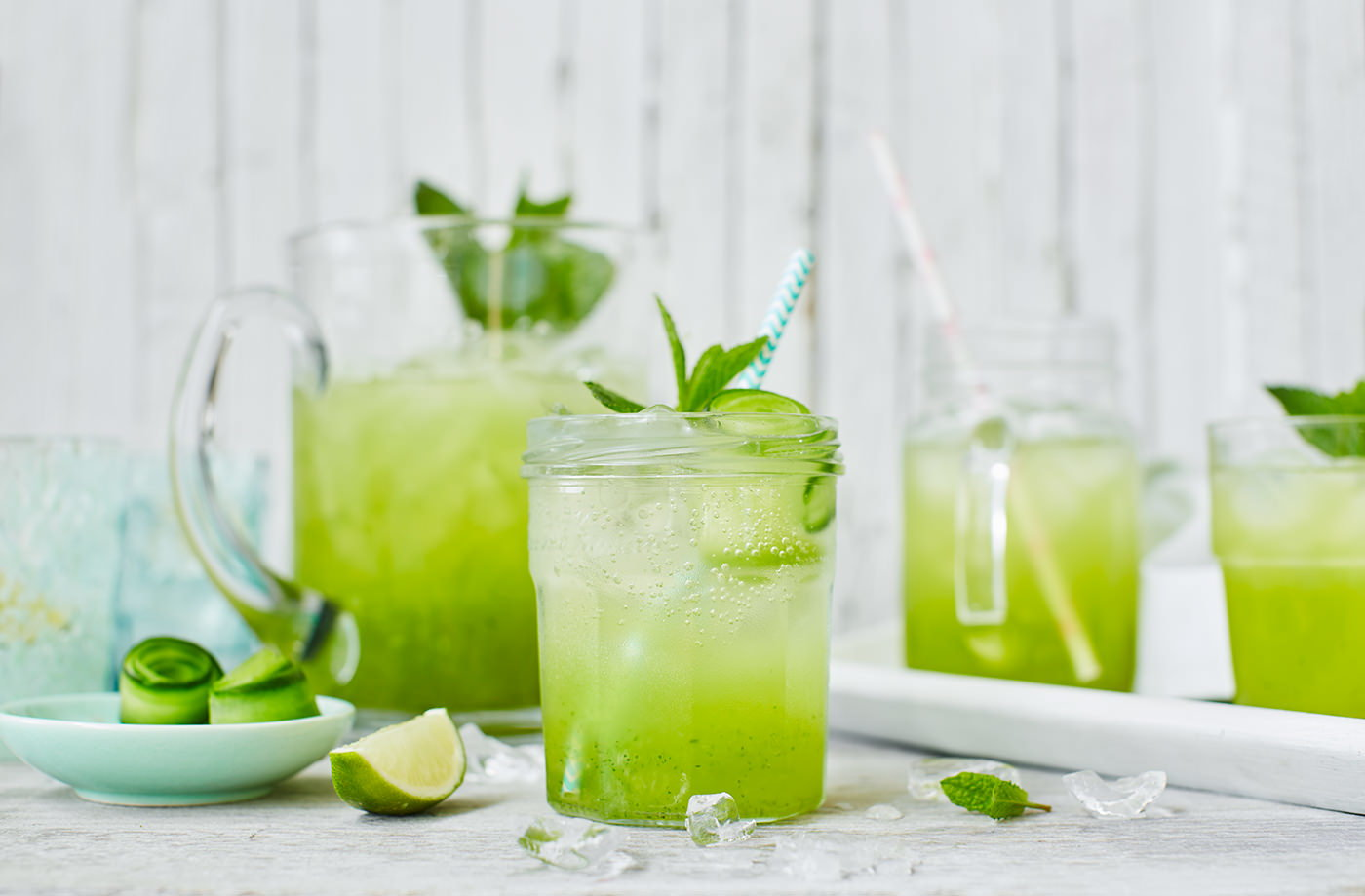 Glass & pitcher full of cucumber, lime & elderflower cooler garnished with mint and lime