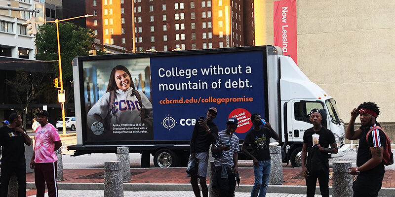 """truck-side ad by CCB, with a student posing with the university's hoodie and the text, """"College without a mountain of debt."""""""