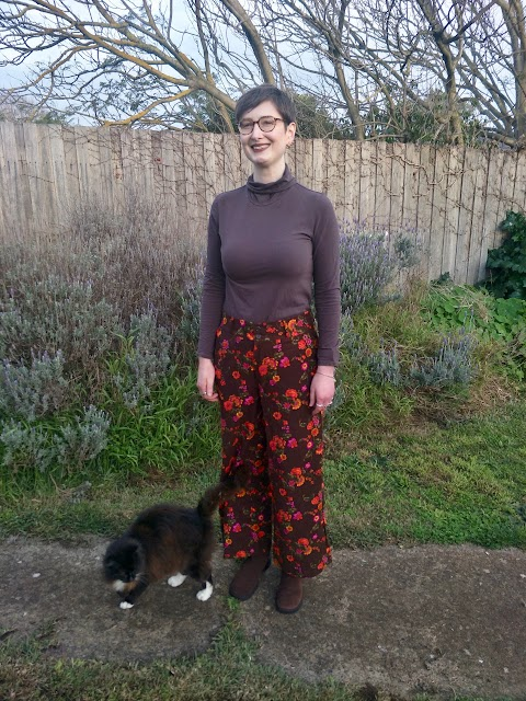 Siobhan stands in front of a garden fence. She wears a brown turtleneck long sleeve top, brown with orange and pink floral print wide leg high waisted pants, brown block heel boots, and tortoiseshell glasses. She is accompanied by a black and white cat, and is smiling.