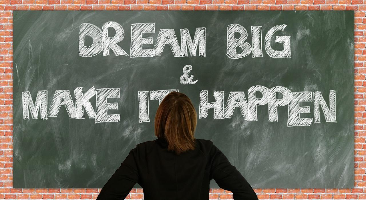 """Woman standing in front of a chalk board that reads """"Dream big and make it happen"""""""