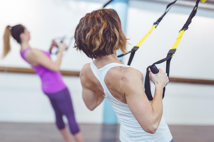 Women Using TRX Straps in Studio