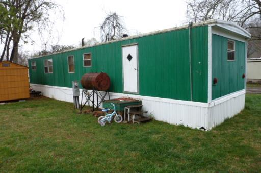 A green wood paneled mobile home