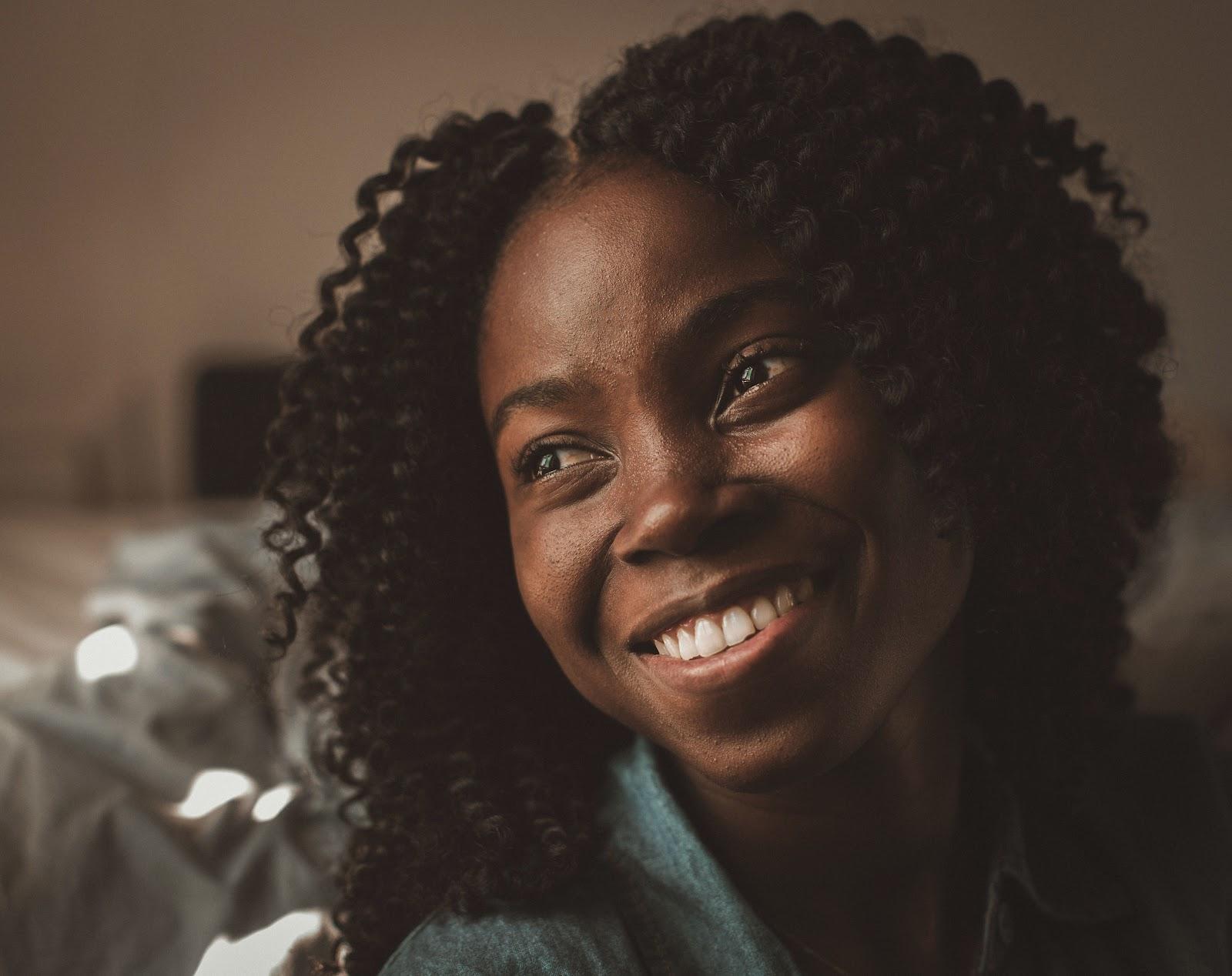Frau mit klarer Haut schaut lächelnd zur Seite