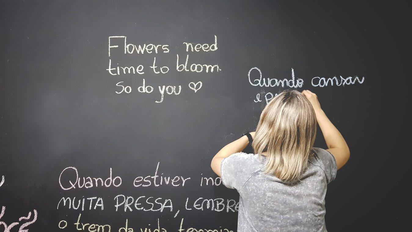 Child writing multiple languages blackboard