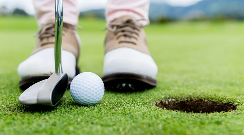 image of someone wearing golfing shoes and putting a golf ball.