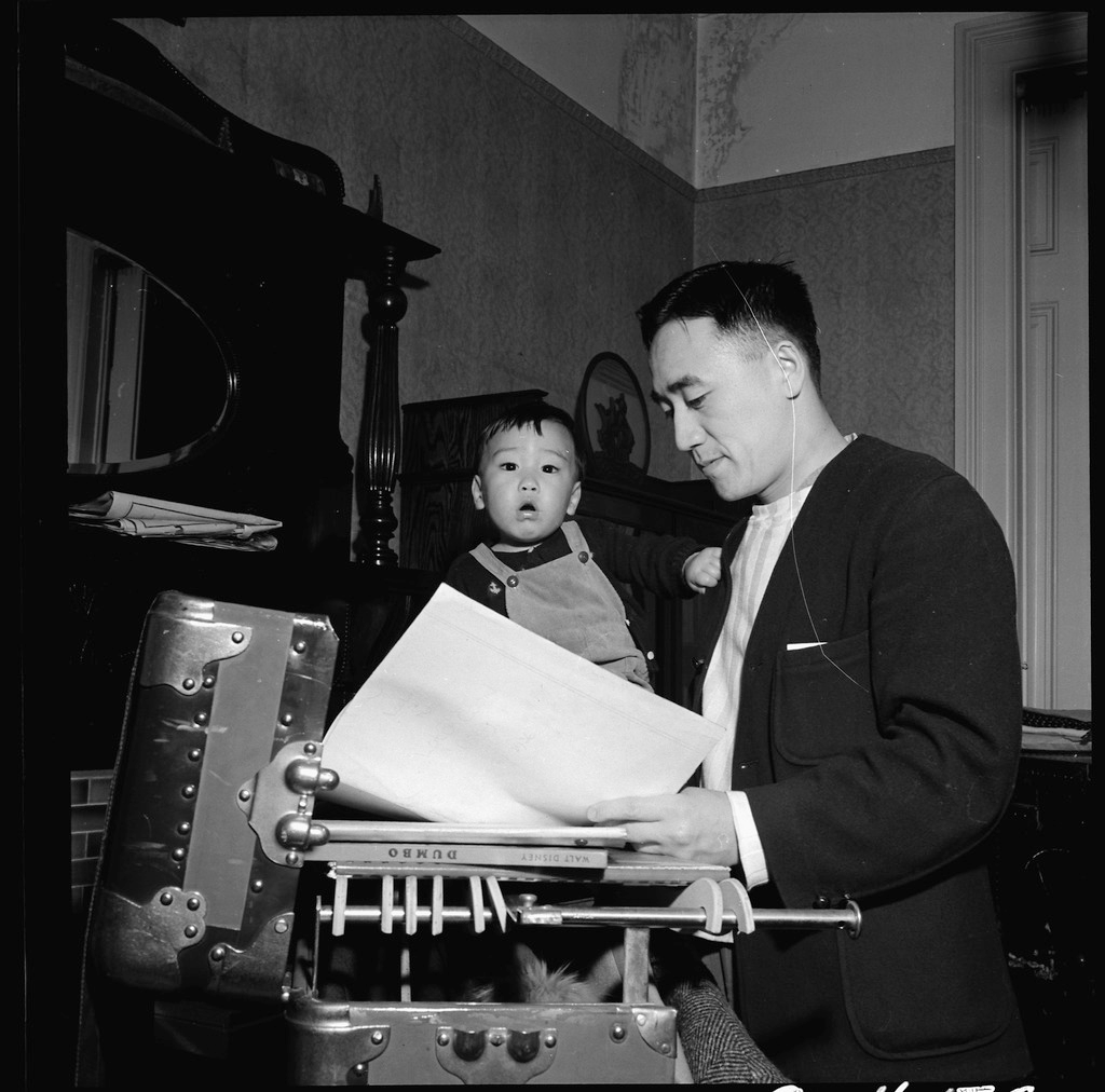 Dave Tatsuno holding his toddler son while preparing for the family's forced removal from San Francisco in 1942. He is looking at sheets of paper in front of an open trunk.