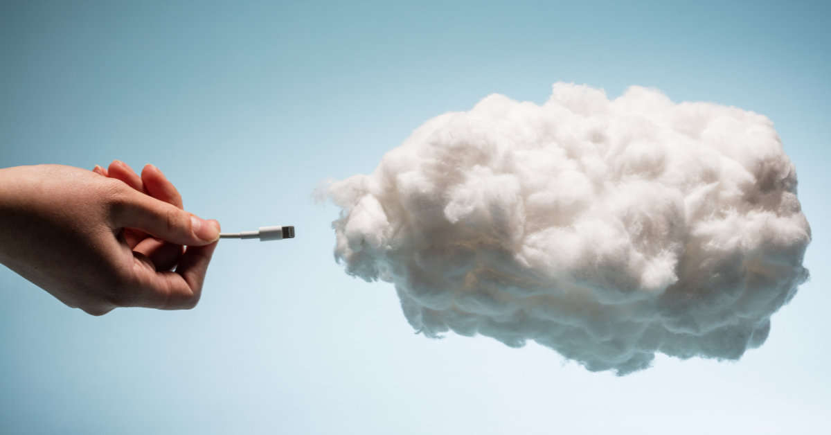 A hand plugging a USB cable into a cloud to symbolize cloud-based services