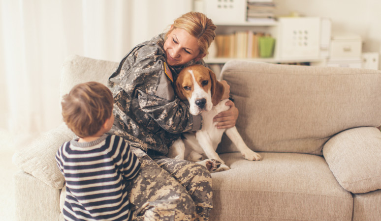 A military woman hugging her dog and talking to her toddler