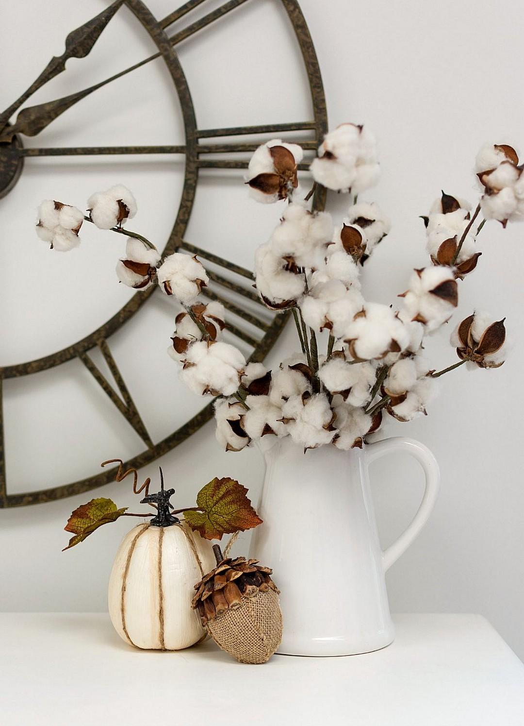 white countertop with pumpkin decor and white vase holding cotton flowers