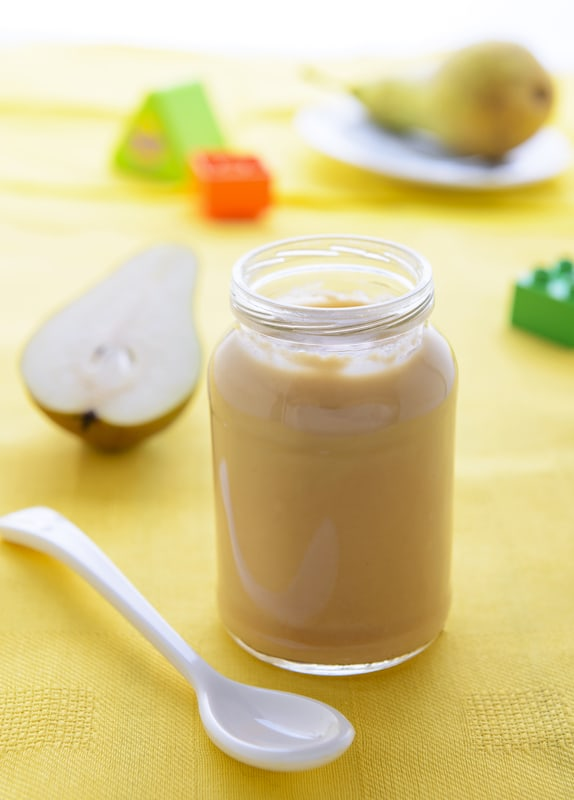 pear puree: one of the must-have baby food recipes, served in a glass jar against a yellow background
