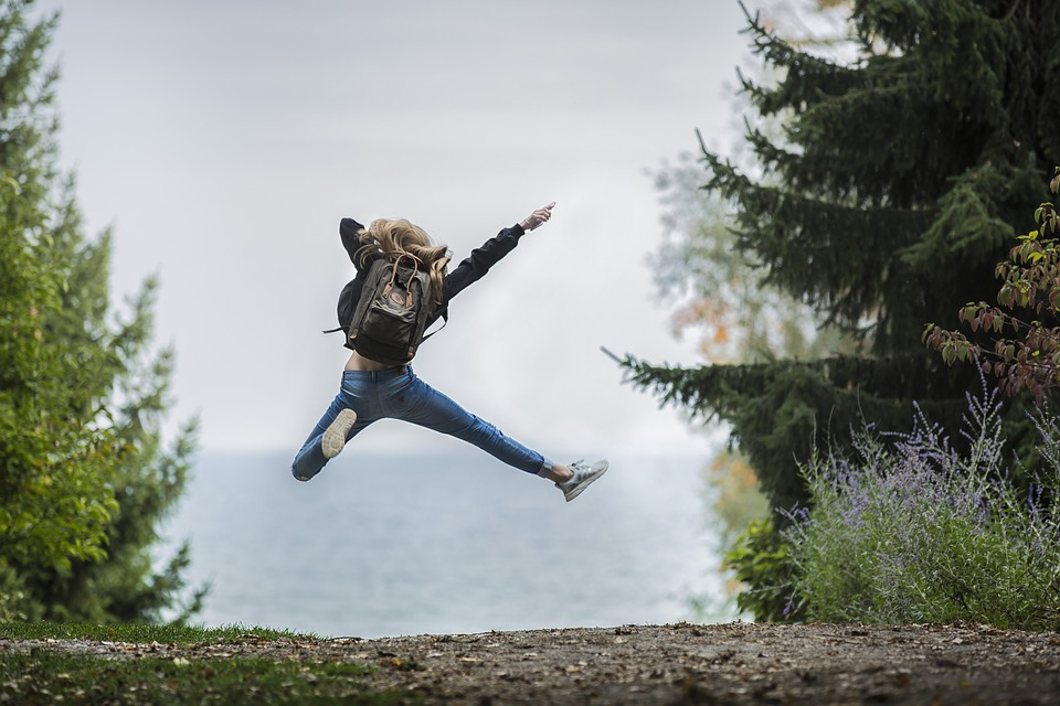 young woman jumping in the air wearing backpack