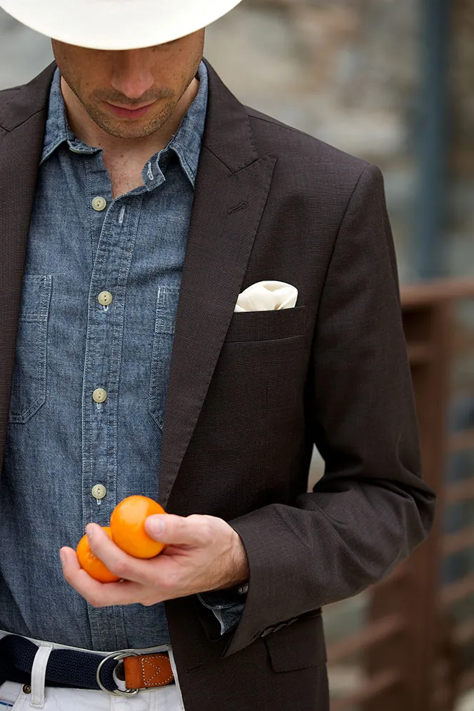 A person wearing a blazer over a chambray shirt along with a white hat.