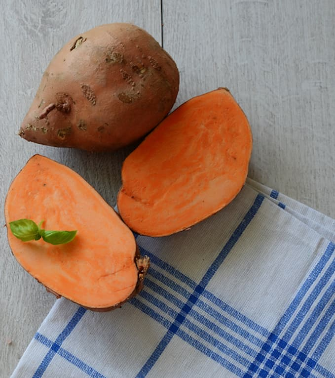 raw sweet potatoes sliced in half, served against a blue checkered napkin