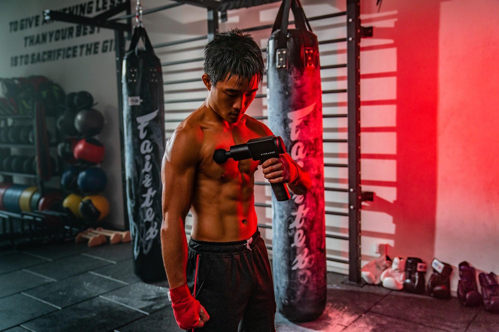 MMA fighter using HYDRAGUN massage gun in the gym