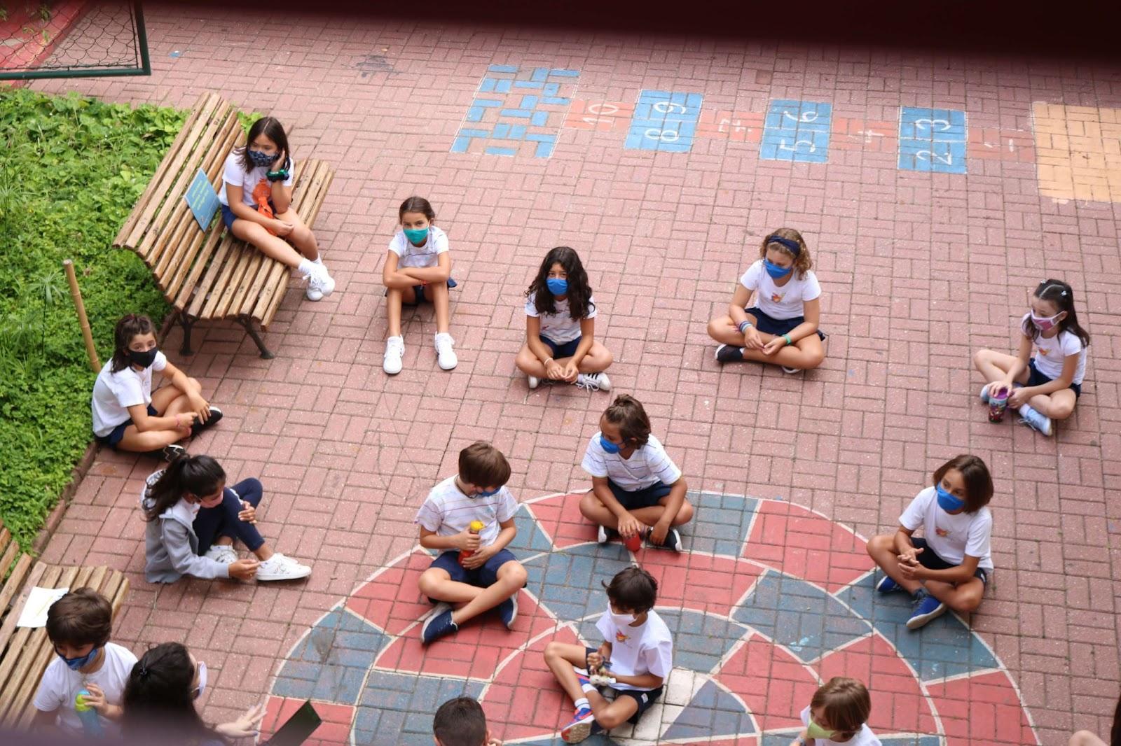 A imagem mostra um grupo de criança sentadas em um chão de tijolos vermelhos.