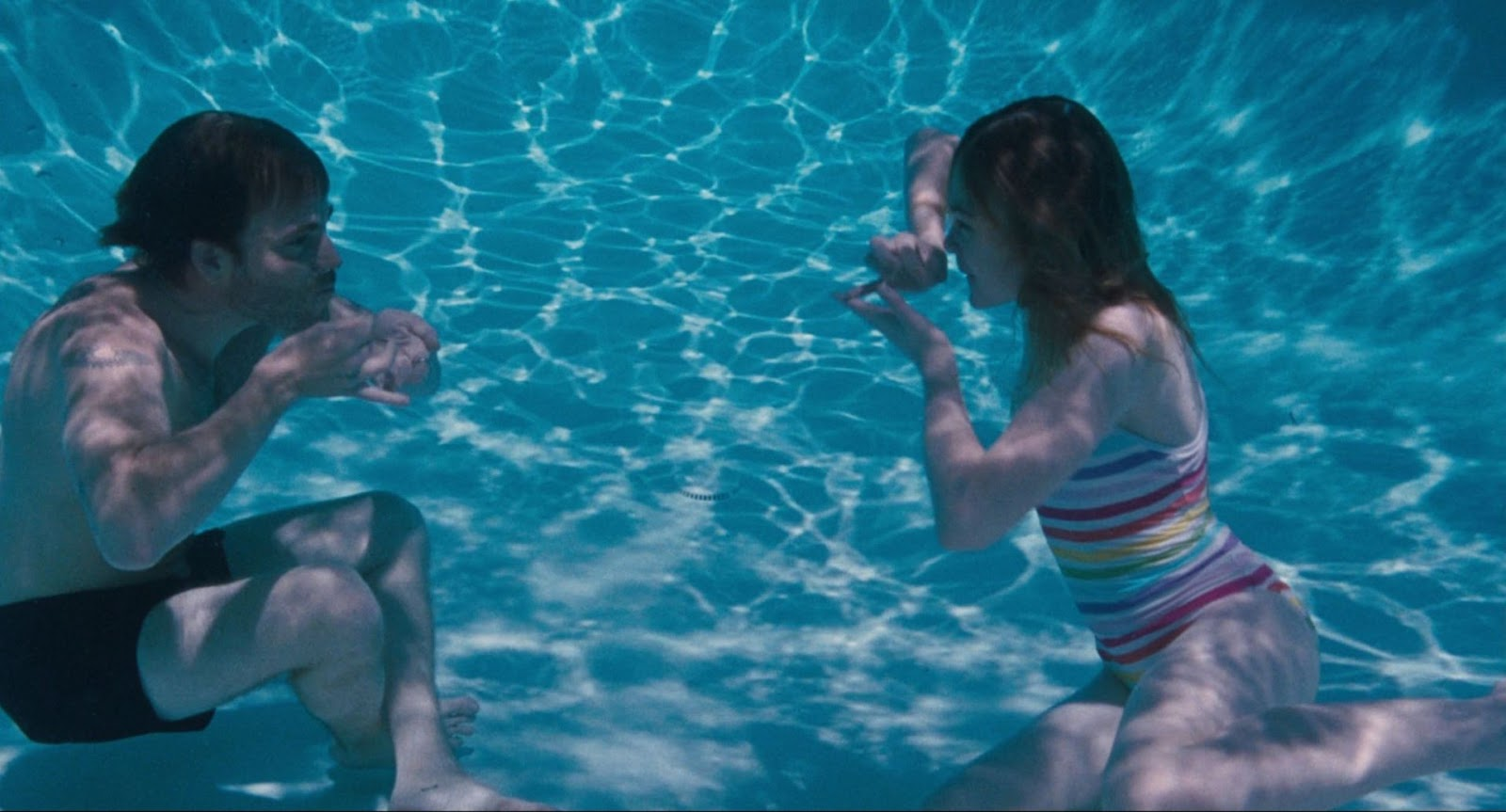 Johnny and Cleo facing each other underwater as they are pretending to have a tea party by mimicking using tea cups and dishes. Johnny is placed to the left of the film still while Cleo is more on the right. Johnny wears black swim trunks and Cleo wears a colourful bathing suit consisting of variations of blue, pink, red, yellow and green hues in horizontal stripes. Johnny is sitting at the bottom of the pool with his legs crossed. Cleo is sitting with her legs folded over on her left side as she leans her body more to her right for balance.
