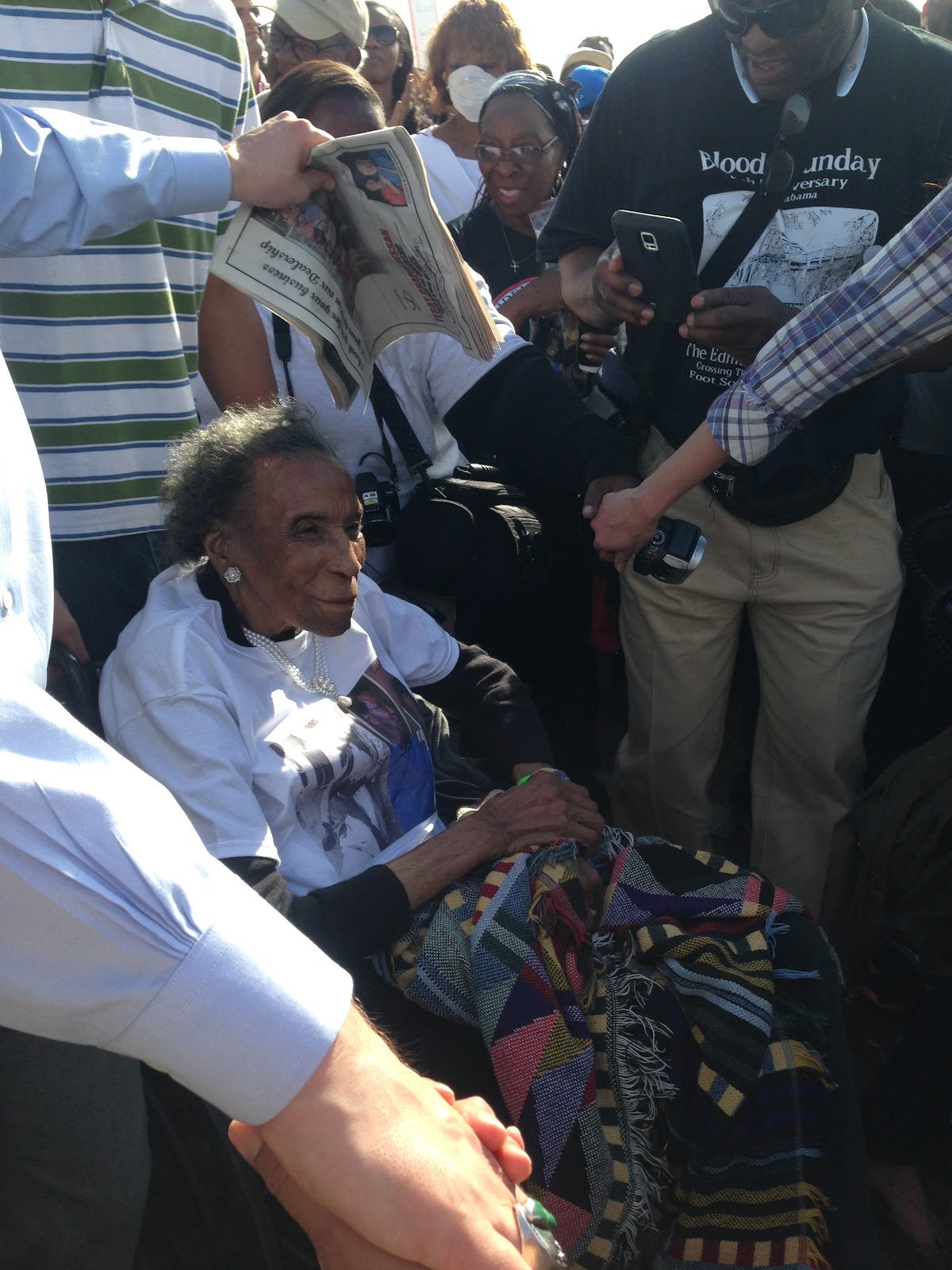 "Amelia Boynton, age 103, is wheeled across the Edmund Pettus bridge during Sunday's commemoration of Bloody Sunday. 50 years ago, she was thrown down and beaten by Alabama state troopers and Selma police. Kirsten West Savali writes of her saying, "" we better climb down from the shoulders of history and get to [the work of today]."" -http://www.theroot.com/</em><em>articles/history/2015/03/"