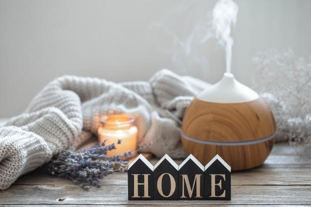 Aroma still life with a modern aroma oil diffuser on a wooden surface with a knitted element, cozy details and the decorative word home. Free Photo