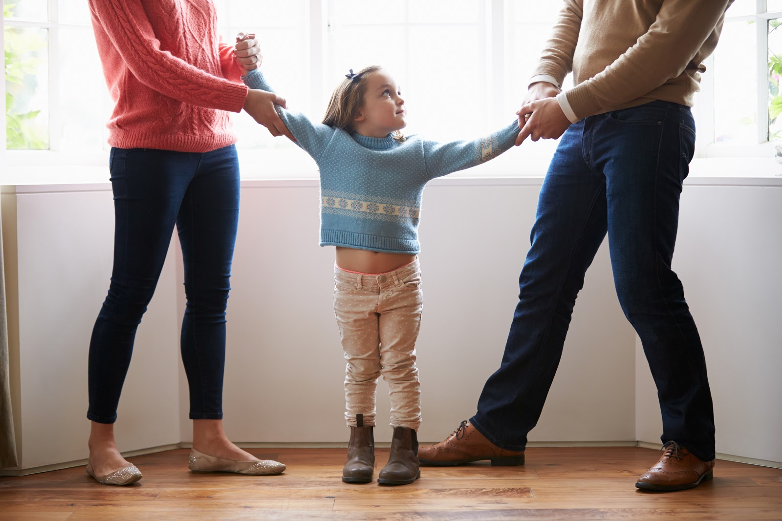 A child being pulled by both parents opposite ways in divorce