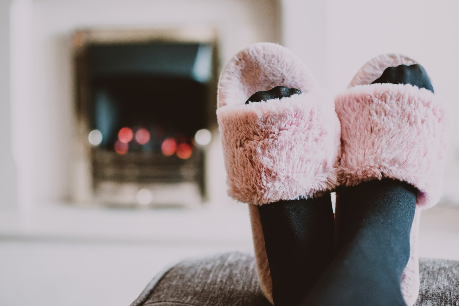 An Image of feet propped up on a comfy sofa while wearing soft slippers