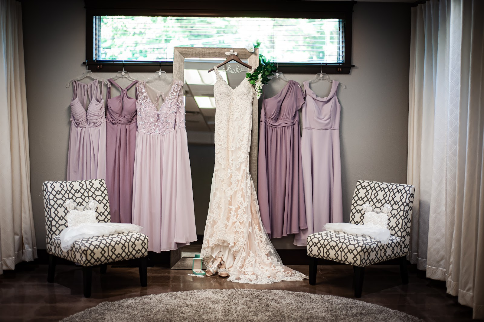 Bridal gown hanging in front of mirror with lavender bridesmaid dresses on either side.