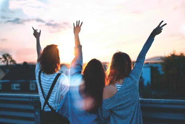 Foto de três amigas, viradas de costas, com os braços levantados