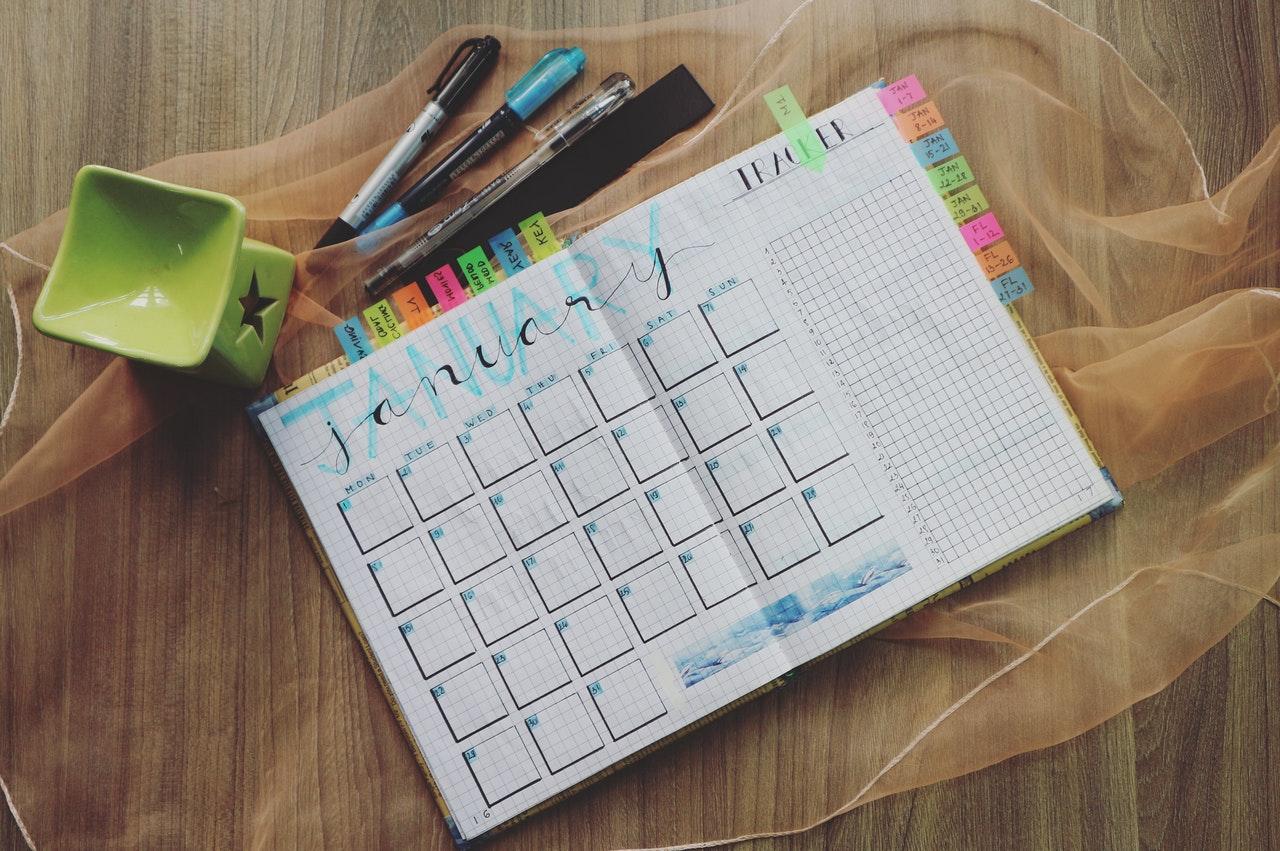 Planer z ręcznie pisanymi notatkami, otwarty na stronach styczniowych, leżący na drewnianym stole