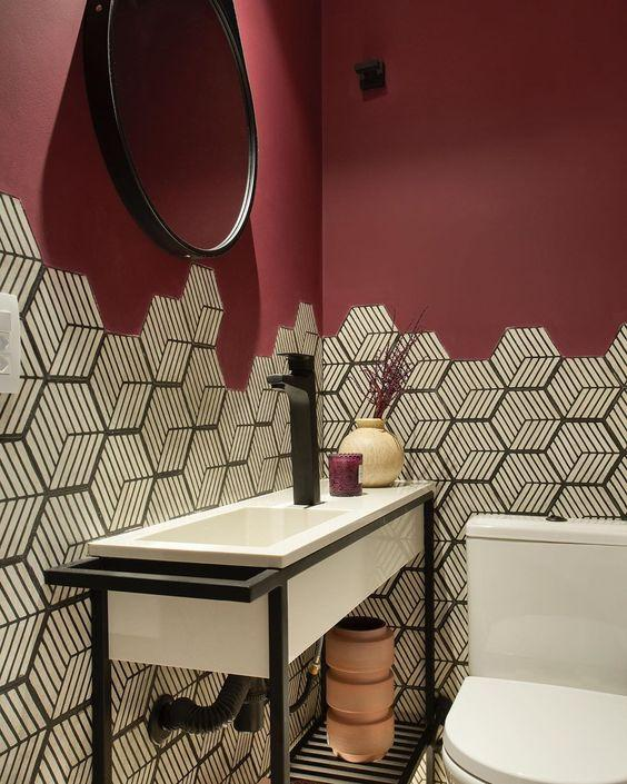 Banheiro com revestimento hexagonal personalizado em preto e branco em meia parede e demais parede pintada de marsala, espelho redondo com moldura preta, bancada da pia branca com estrutura de ferro preta e torneira preta.