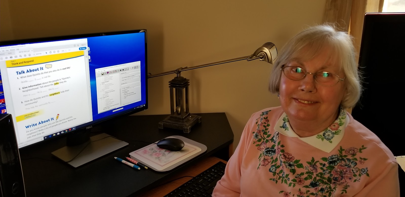 Volunteer Caren Snook smiles as she takes a break from setting up the language arts book (computer screen with book and TOCTool images in background)