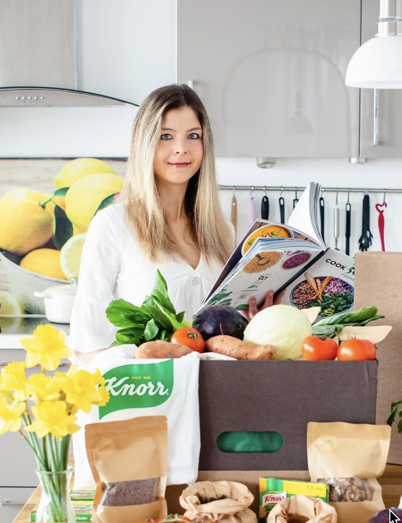 Bianca Zapatka |  Reading a recipe book with bags of veg on the side