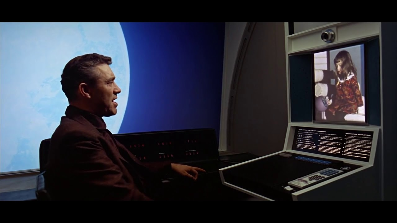 A still from Stanley Kubrick's 2001: A Space Odyssey that shows the inside of a videophone booth with a screen and interface.