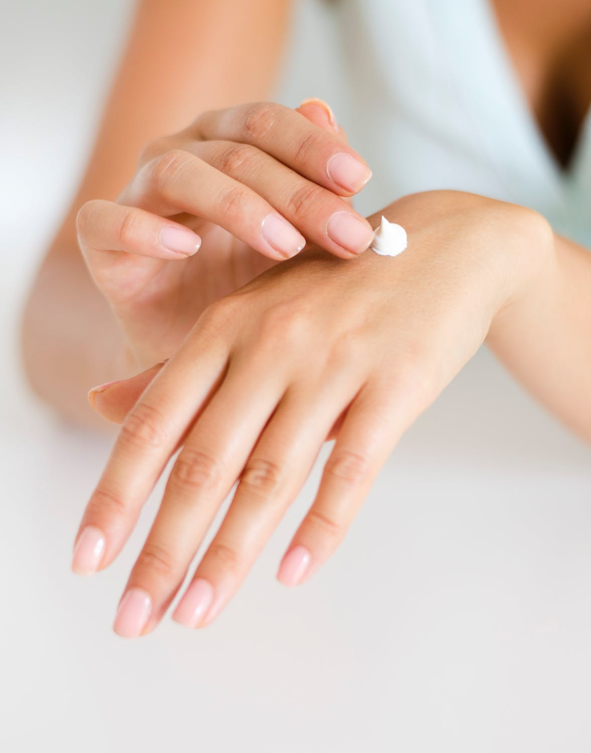 woman applying hand cream to back of hand