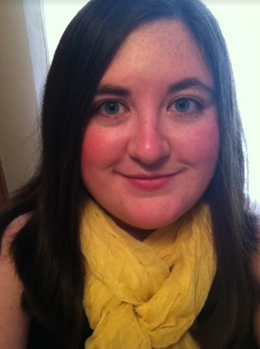 Brunette with long hair wearing a yellow scarf looks into the camera.