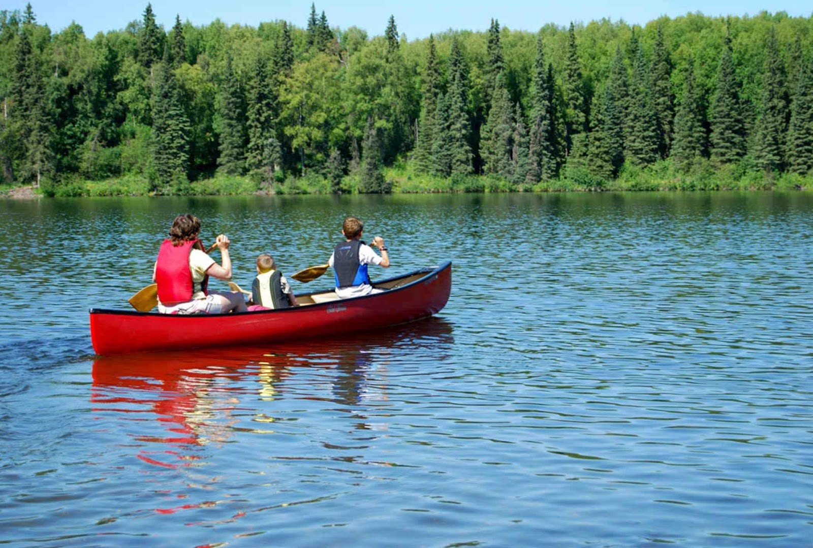 C:\Users\Family\Desktop\An_adult_and_two_children_canoe_on_lake.jpg