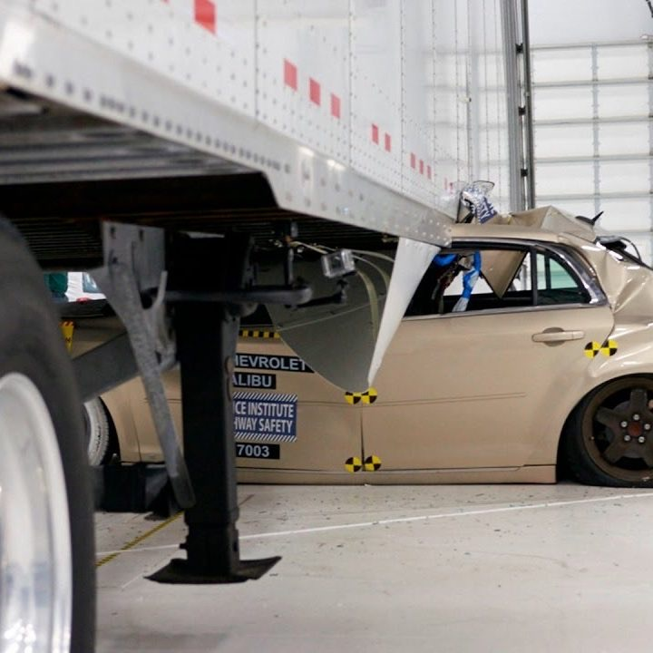 A car that has run into the side of the trailer of a big rig truck