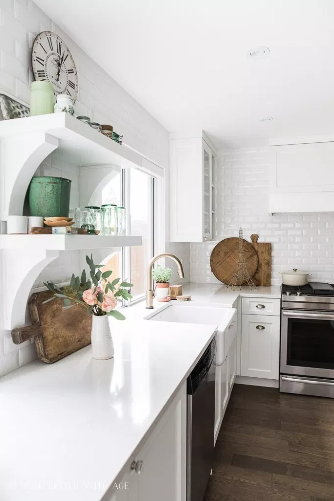 Farmhouse kitchen with white wood cabinets, flooded with natural light. A white subway tile backsplash and bright white countertop complement the white shaker cabinets.
