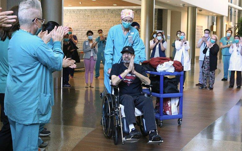 Health care workers applaud Michael Flor upon his release from Swedish Issaquah last month Pushing the wheelchair is Dr. Anne Lipke, Flor's critical care doctor. (Ken Lambert / The Seattle Times)