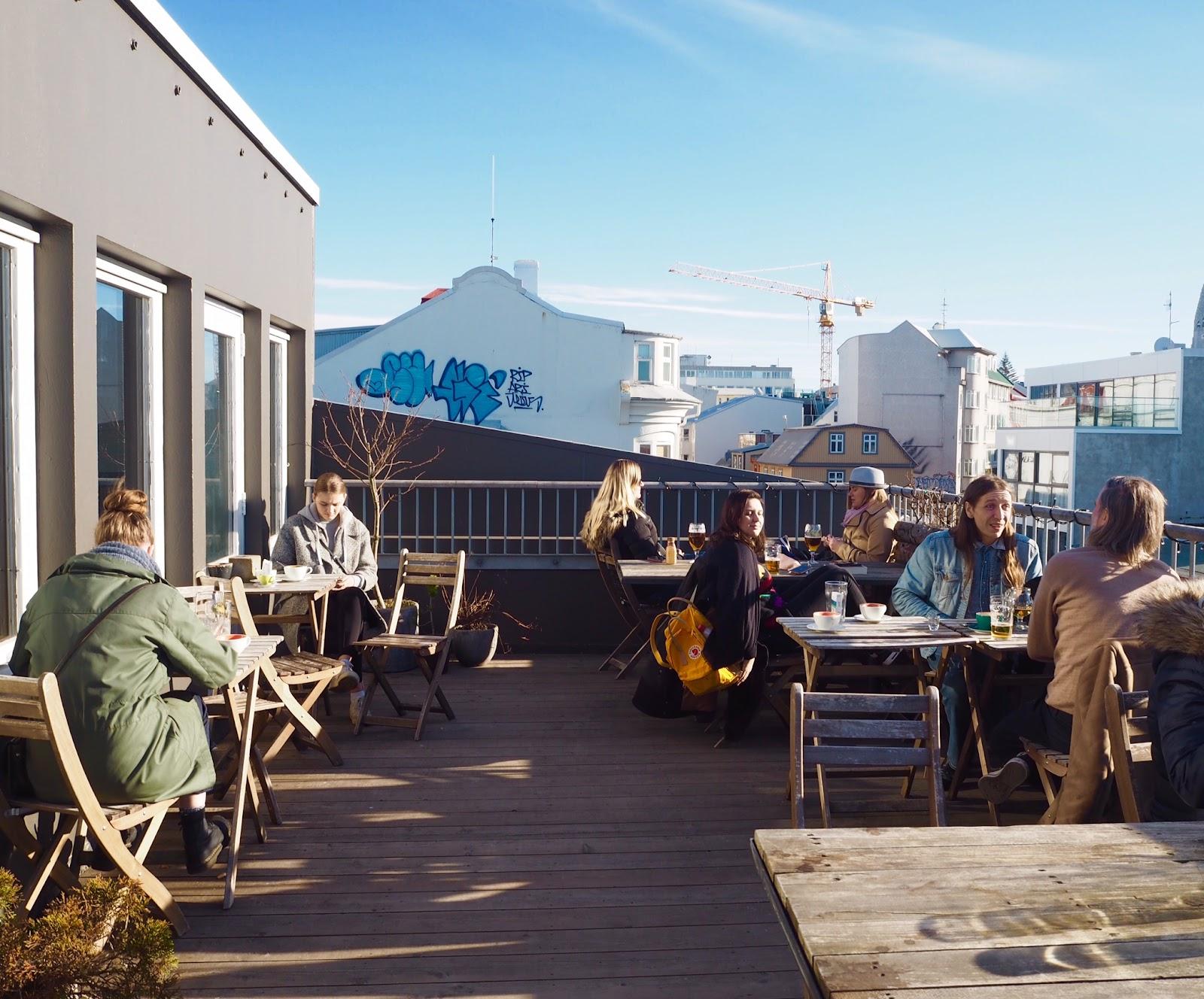 People sitting outside on a balcony at Loft Hostel, Reykjavik.