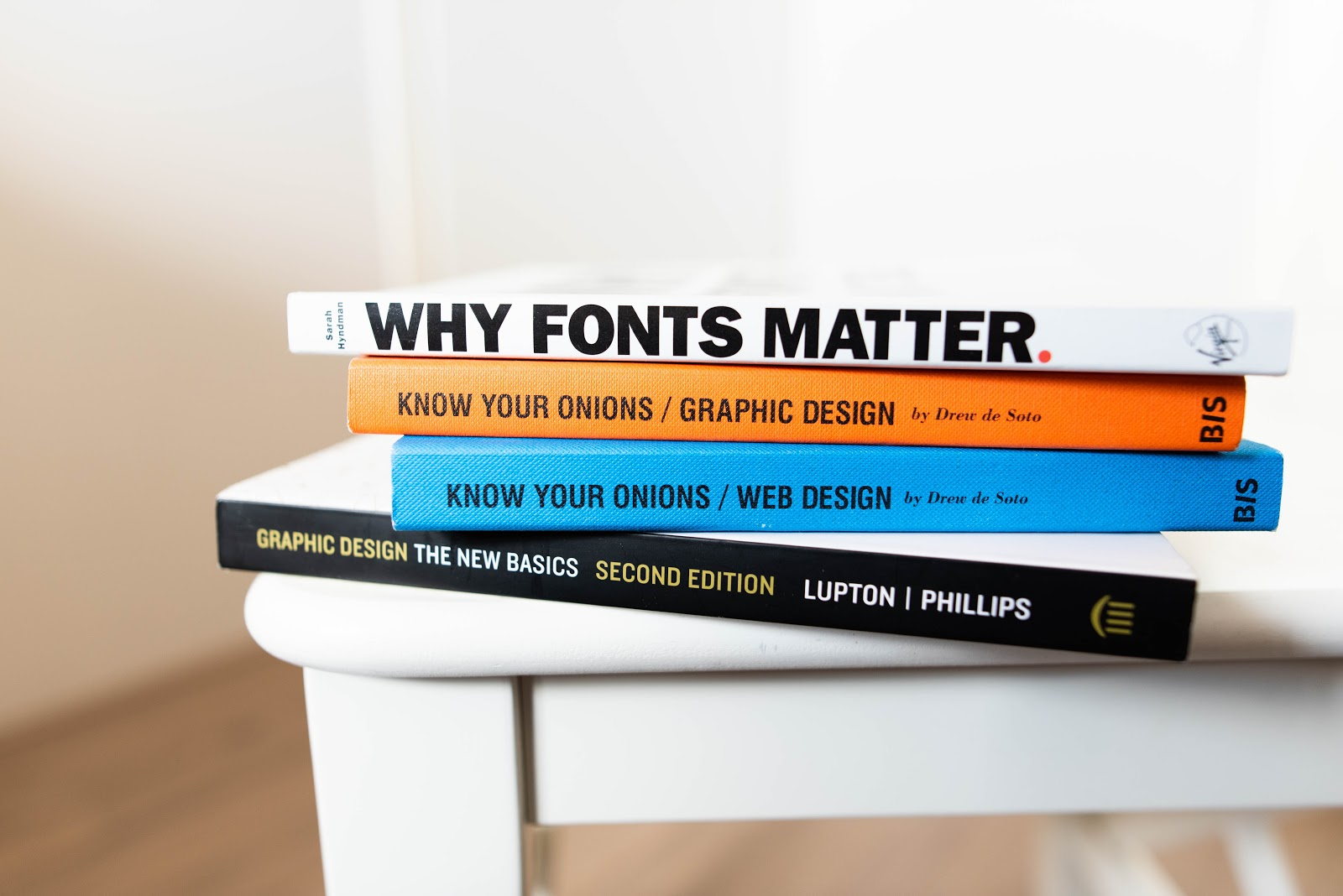 Books about fonts and graphic design stacked on top of a table
