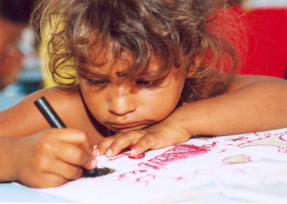 Criança fazendo desenhos.