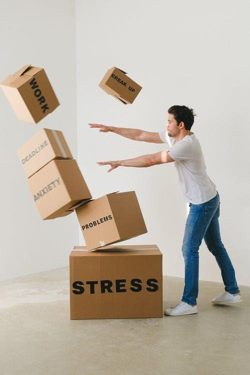 Full body of young man in sneakers and jeans pushing and falling boxes saying Work Problems Anxiety Stress and Deadline while fighting with problems