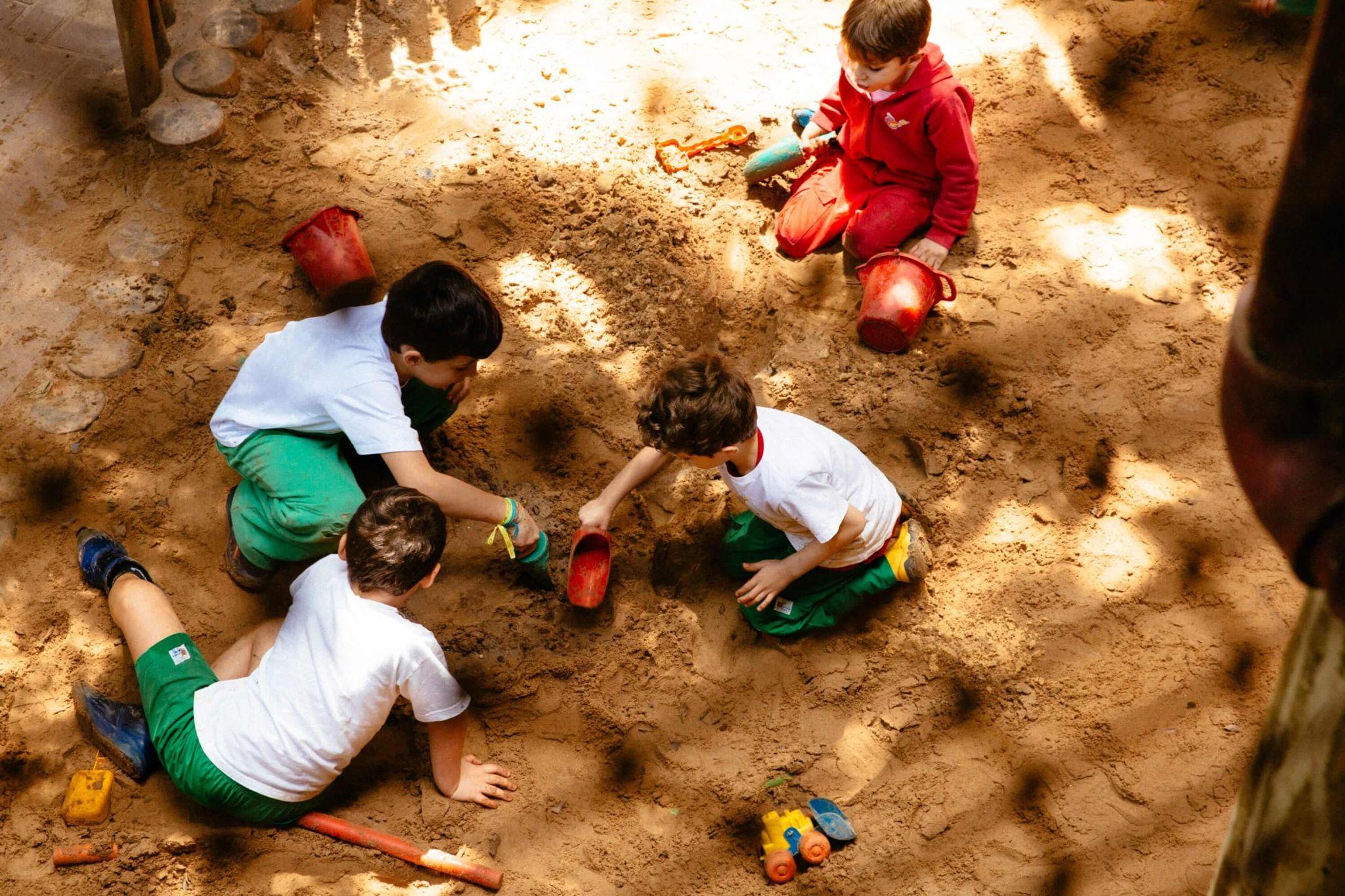 A imagem mostra um grupo de crianças brincando na terra.