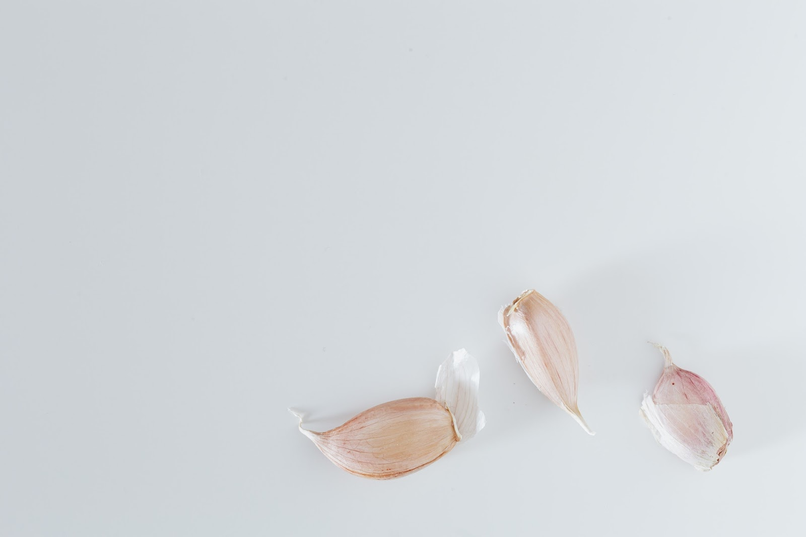 Three cloves of garlic on a table.