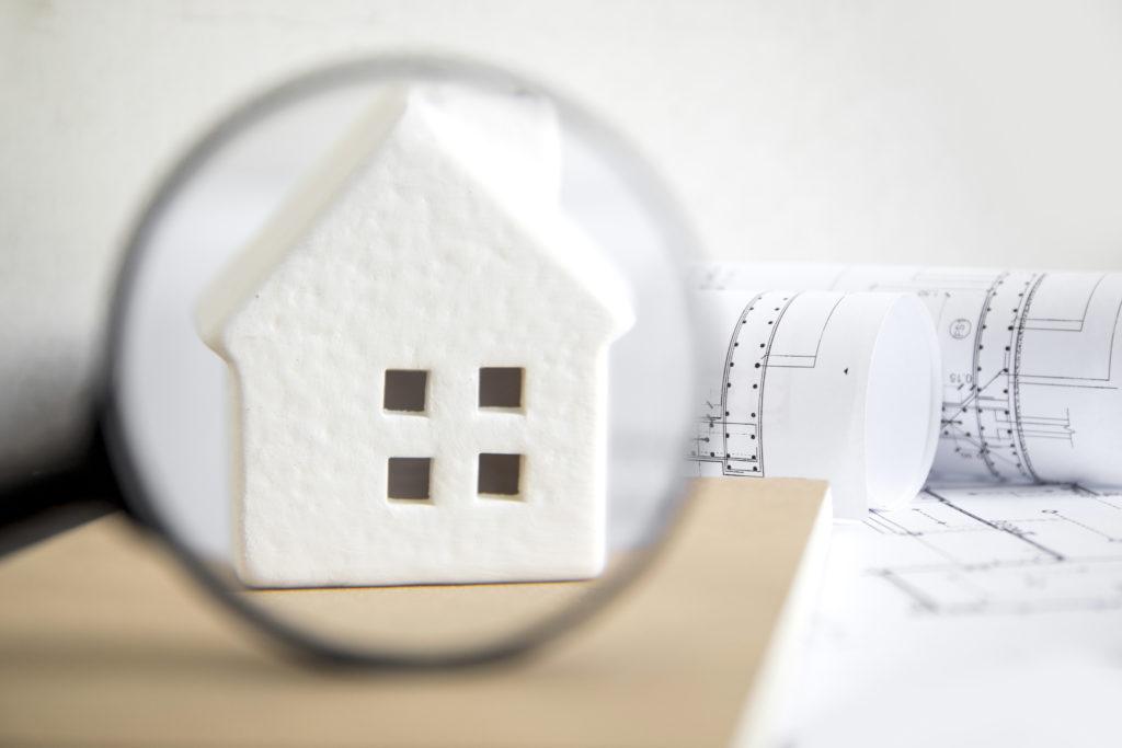 petite maison blanche vue à la loupe à côté de papier de plans de maison et d'investissement immobilier devant un mur blanc