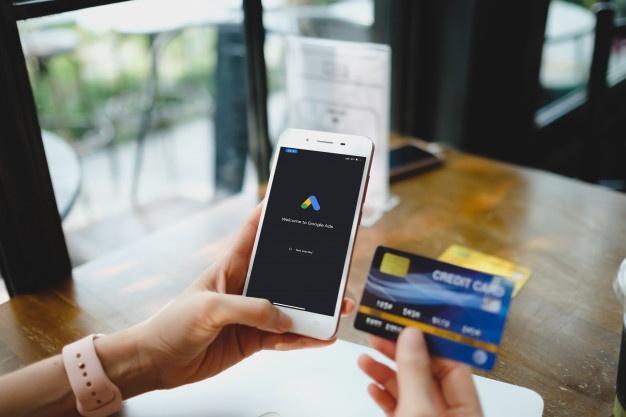 Mulher está digitando no google ads e cartão de crédito a partir de um telefone celular.