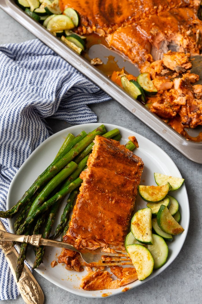 A plate with cajun butter baked salmon with vegetables