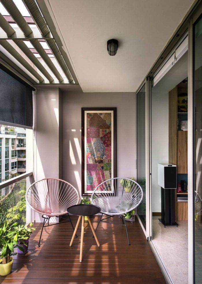 varanda bem arejada com piso de madeira, cadeiras branca e rosa, mesinha redonda preta, vaso de plantas no chão e quadro na parede.