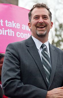 An upclose shot of Washington State Senator Kevin Ranker in front of a pink sign. Ranker is wearing a gray suit, white shirt, and gray and white striped tie.